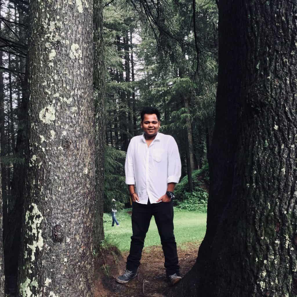 Vipin, standing between two Deodar trees.